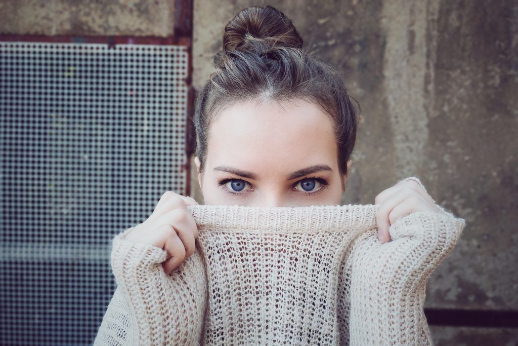 Woman pulling her sweater over her face