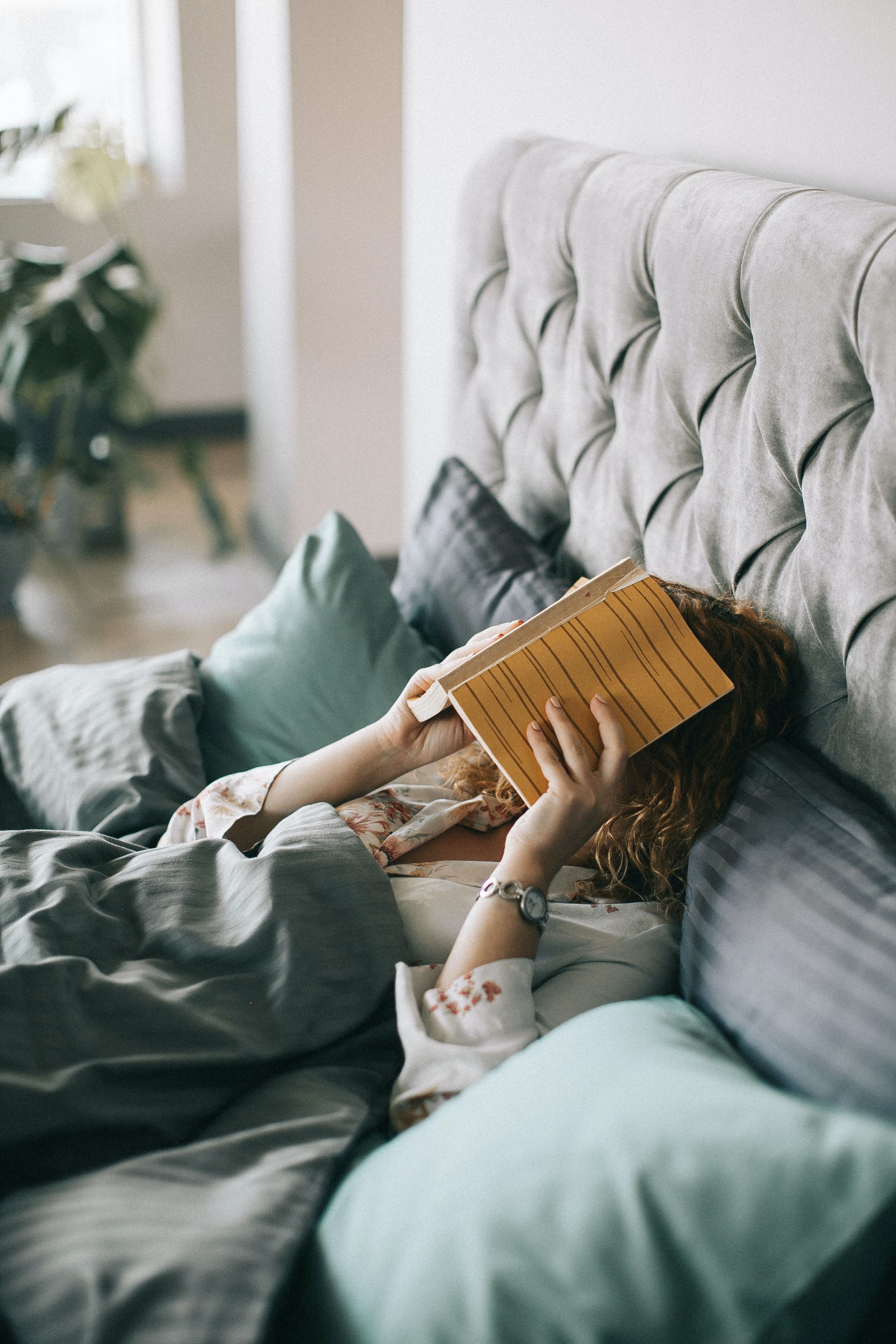 Woman in bed with a book over her face