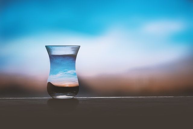 A glass of water with a sunset view behind it