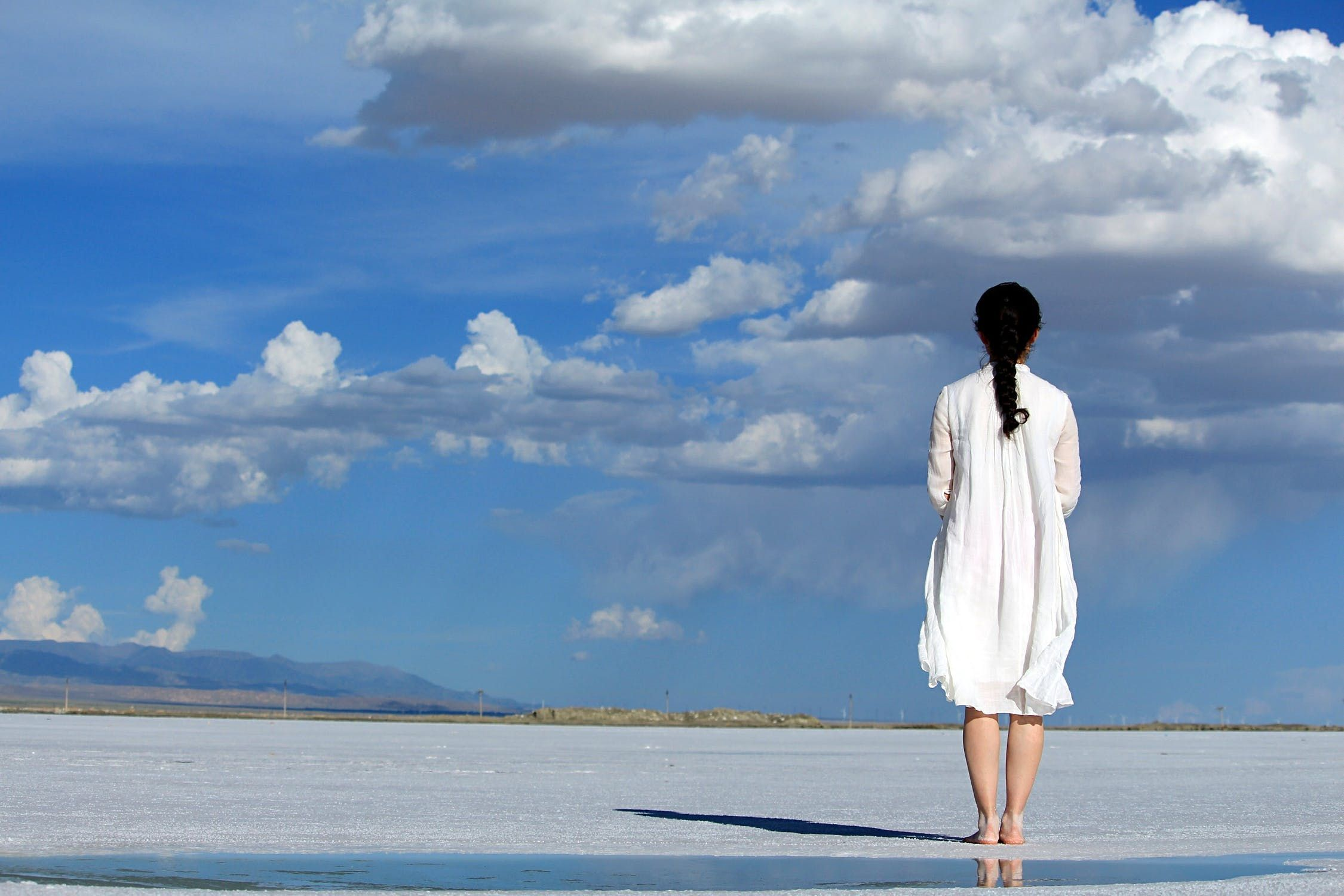 Woman standing on beach looking into the distance