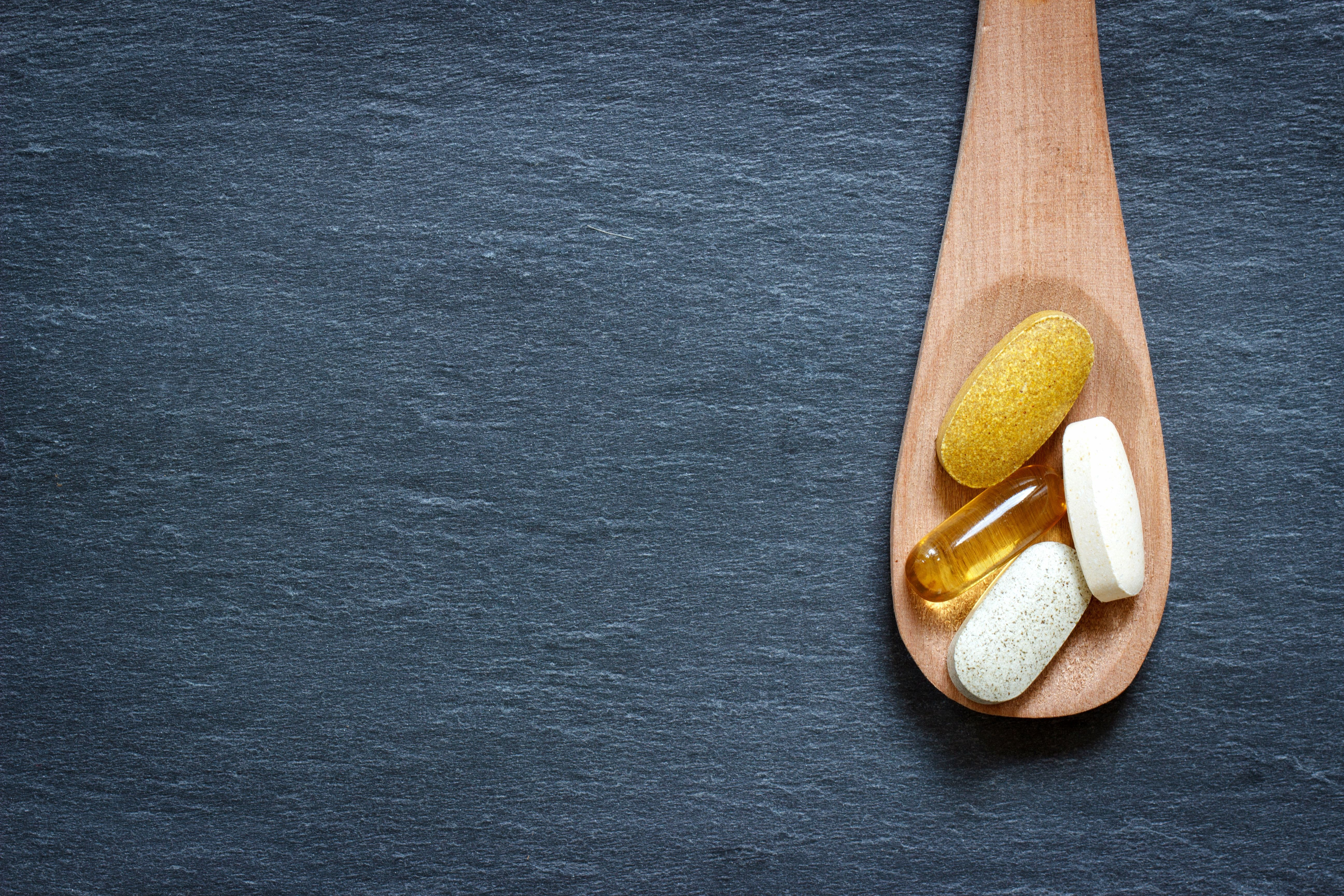 Variety of supplements in wooden spoon